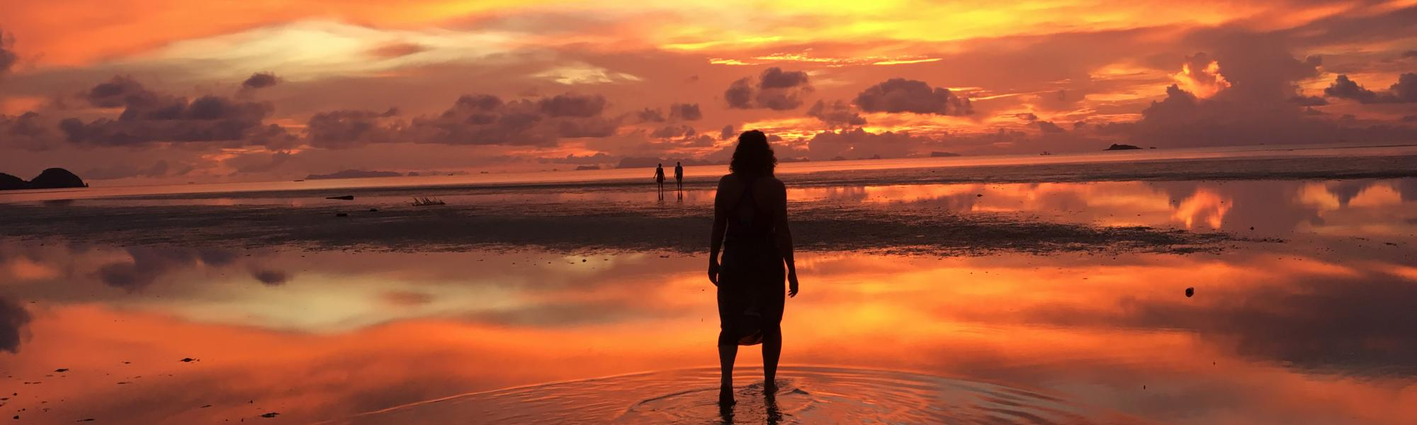 Person standing in front of vibrant sunset.